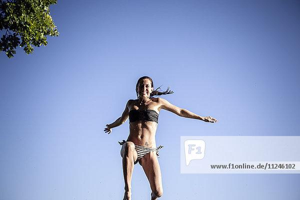 Frau im Bikini springt in der Luft