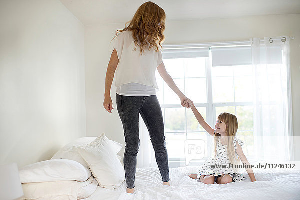 Mother and daughter playing on bed together