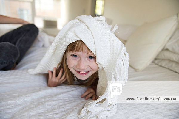 Young girl peeking head out from under blanket on bed