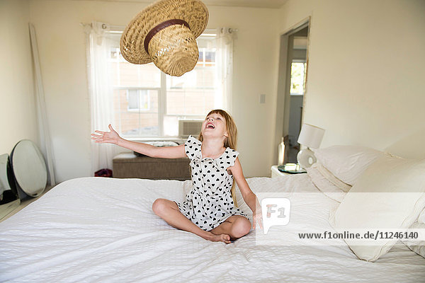 Young girl sitting on bed  throwing straw hat up in air
