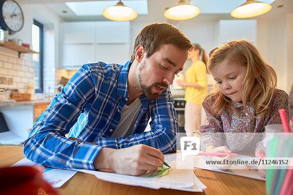 Mittelgroßer erwachsener Mann und Tochter malen am Tisch in der Küche