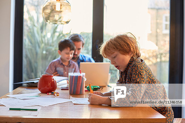 Boy colouring at dining table whilst father using laptop with brother