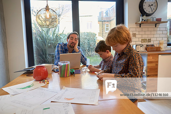 Exhausted man at dining table with laptop whilst son colouring