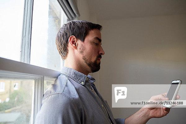 Mid Erwachsene Mann am Fenster lesen Smartphone-Texte