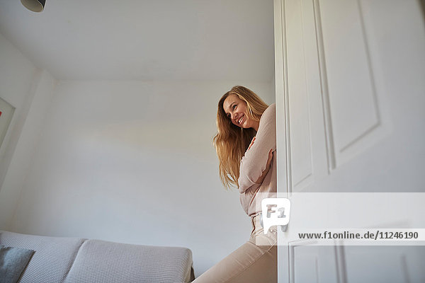 Porträt einer Frau mittleren Alters  die sich an die Wohnzimmertür lehnt