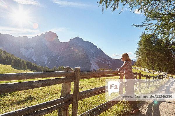 Reife Frau lehnt am Zaun mit Blick auf die Dolomiten  Sexten  Südtirol  Italien