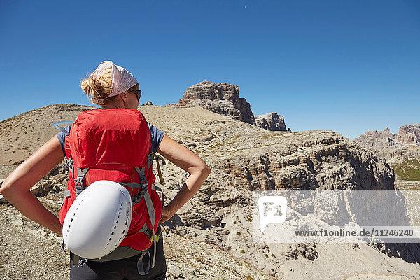 Rückansicht einer Wanderin mit Händen auf den Hüften in den Dolomiten  Sexten  Südtirol  Italien