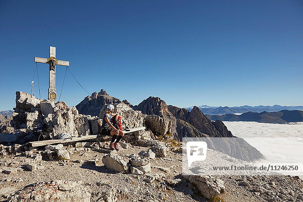 Female hiker sitting on Paternkofel mountain bench  Dolomites  Sexten  South Tyrol  Italy