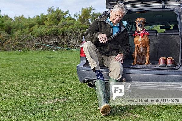 Mann und Hund sitzen im Kofferraum und ziehen Gummistiefel aus