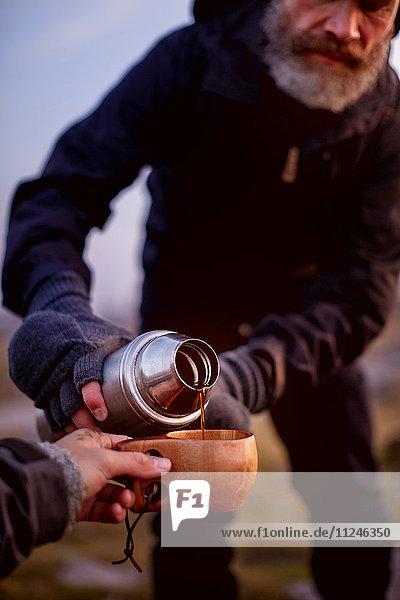 Wanderer schüttet Kaffee in die Tasse eines Freundes