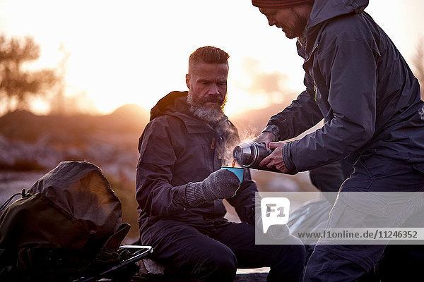 Wanderer schüttet Kaffee in die Tasse eines Freundes  Sarkitunturi  Lappland  Finnland