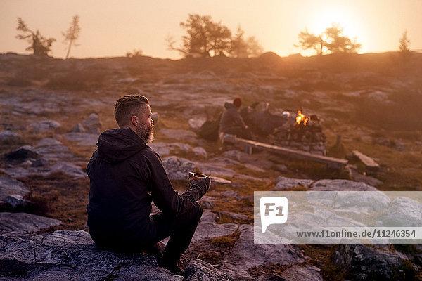 Wanderer entspannt bei Kaffee auf felsigem Feld  Sarkitunturi  Lappland  Finnland