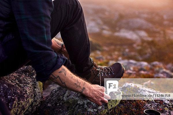 Wanderer bindet Schnürsenkel auf felsigem Feld  Sarkitunturi  Lappland  Finnland