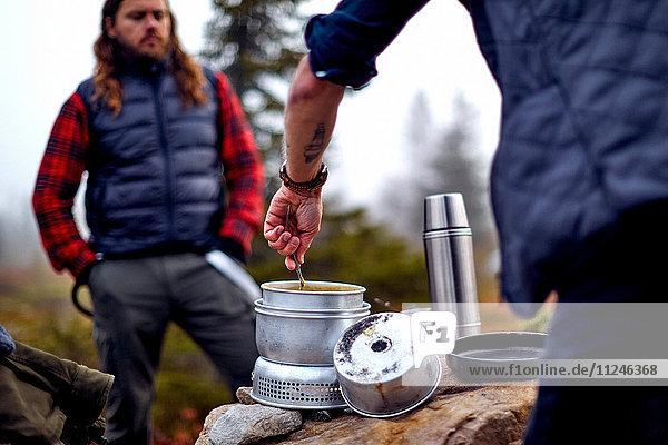 Wanderer betrachtet Freund beim Kochen  Sarkitunturi  Lappland  Finnland