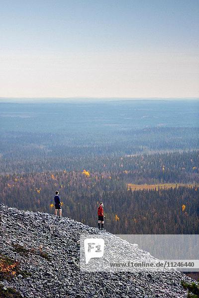 Wanderer mit Aussicht auf felsigen Steilhang  Kesankitunturi  Lappland  Finnland