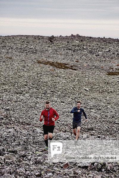 Männer laufen auf felsiger Felsspitze  Kesankitunturi  Lappland  Finnland
