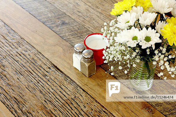 Wooden table in coffee shop with flower arrangement and salt & pepper