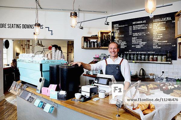 Porträt eines männlichen Geschäftsinhabers hinter der Theke eines unabhängigen Cafés