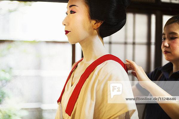 Eine moderne Geisha- oder Maiko-Frau  die in traditioneller Weise in einer weißen Schicht mit losem Kragen gekleidet ist  mit weißem Gesichtsschminke.