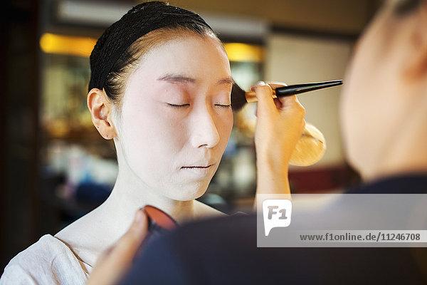 Eine moderne Geisha oder Maiko-Frau  die auf traditionelle Weise vorbereitet wird  mit weißem Gesichts-Make-up.