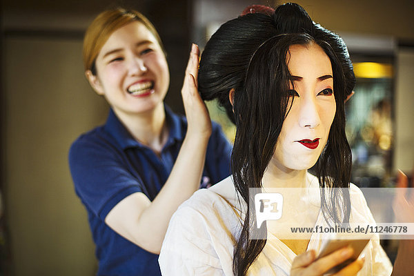A geisha or maiko with a hair and make up artist creating the traditional hair style and make up.
