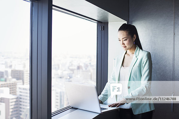 A business woman by a window using her laptop.