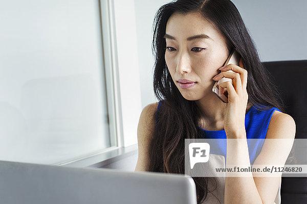 Eine Geschäftsfrau  die sich auf die Arbeit vorbereitet  mit ihrem Laptop sitzt und mit ihrem Smartphone spricht.