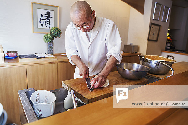 A chef working in a small commercial kitchen  an itamae or master chef slicing fish with a large knife for making sushi