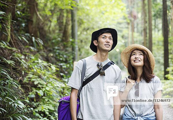 Lächelnde junge Frau und Mann stehen in einem Wald.