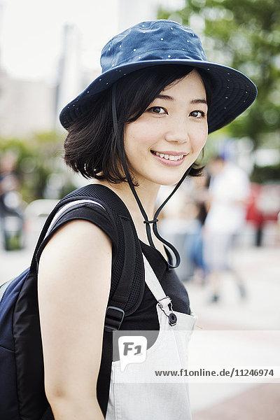 Porträt einer lächelnden jungen Frau mit Hut.
