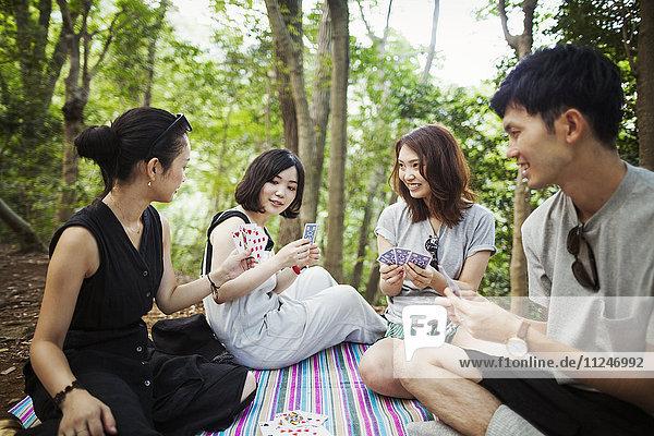 Drei junge Frauen und ein Mann sitzen in einem Wald und spielen Karten.
