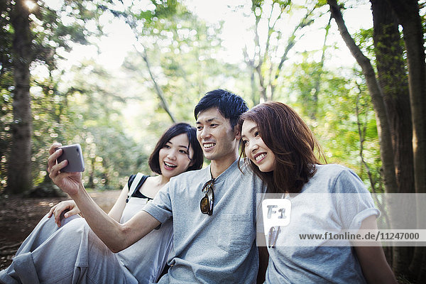 Two young women and a man sitting in a forest  taking a selfie.