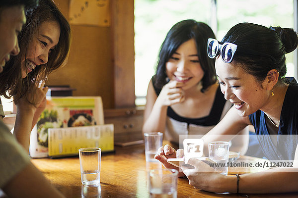 Drei junge Frauen und ein Mann sitzen in einem Cafe.