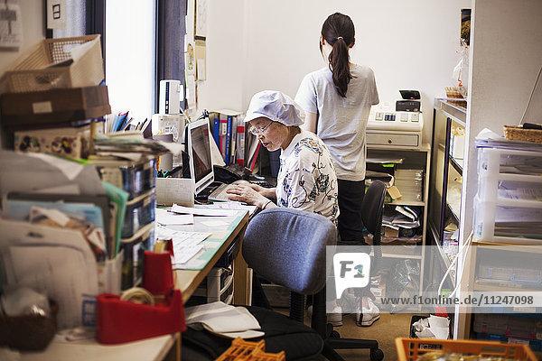 Eine reife Frau an einem Schreibtisch im Büro einer Fastfood-Einheit und Nudelproduktionsfabrik.