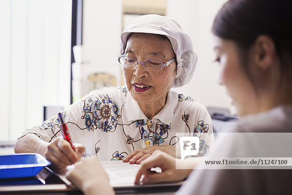 A mature woman at a desk in the office of a fast food unit and noodle production factory.