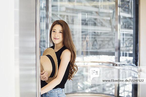 Lächelnde junge Frau mit langen braunen Haaren  Panamahut haltend.