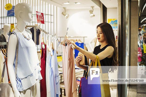 Lächelnde junge Frau mit langen braunen Haaren in einem Bekleidungsgeschäft.