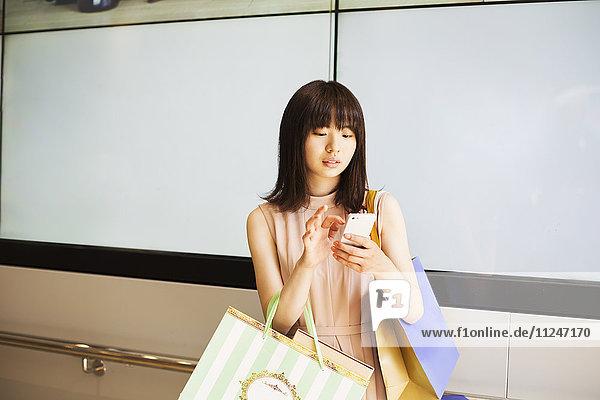 Junge Frau mit langen braunen Haaren  die ein Mobiltelefon und Einkaufstaschen hält.