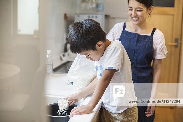 Familienhaus. Eine Mutter und ihr Sohn stehen an einem Waschbecken.