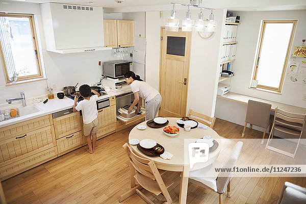 Familienhaus. Eine Frau  die sich bückt  um Geschirr in einem Küchenschrank zu erreichen.