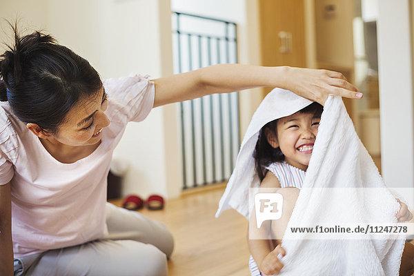 Familienhaus. Eine Frau und ihre Tochter falten saubere Wäsche.