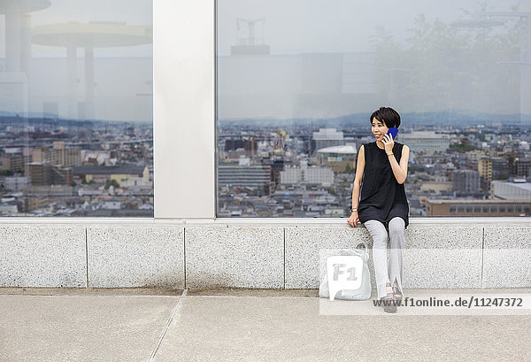 A woman seated by a window with a view over a large city with her back to the view  making a call on a smart phone.