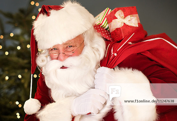 Portrait of Santa Claus carrying sack over shoulder