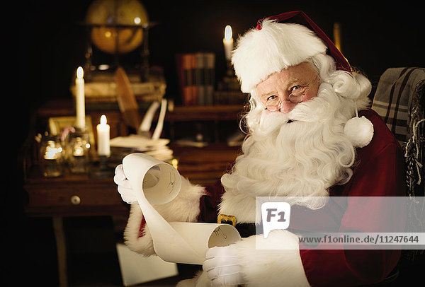 Portrait of Santa Claus reading child's letter