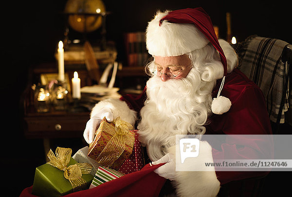 Santa Claus packing Christmas presents to sack