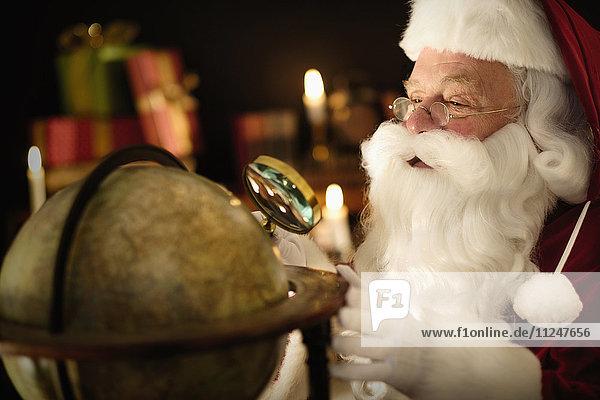Santa Claus looking through magnifying glass at globe