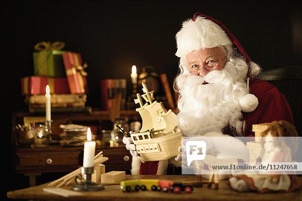 Santa Claus making wooden toy