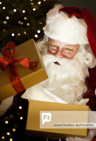 Portrait of Santa Claus opening Christmas presents