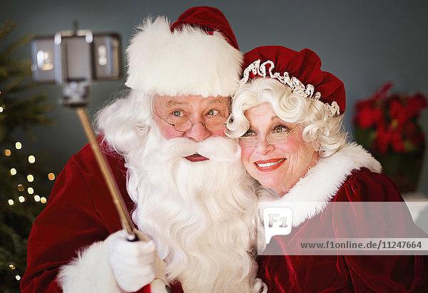 Santa and Mrs. Santa taking selfie with monopod