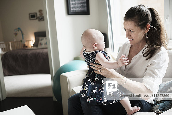 Mother playing with baby daughter (2-5 months) in living room